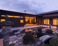 日本庭園を囲む二世帯それぞれの住まい写真(夕景)